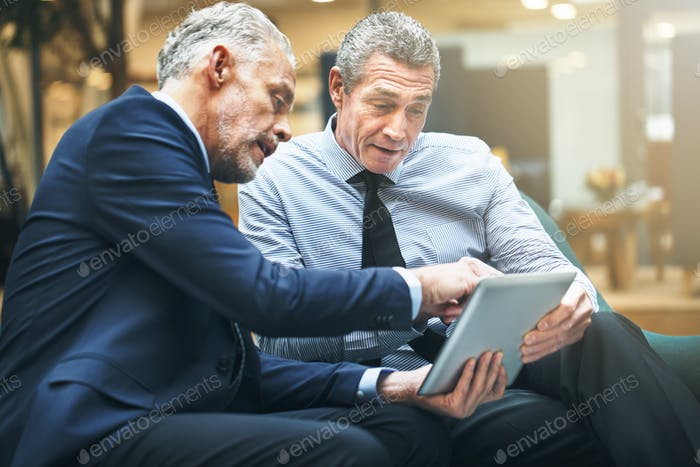 Two mature businessmen discussing work on a digital tablet