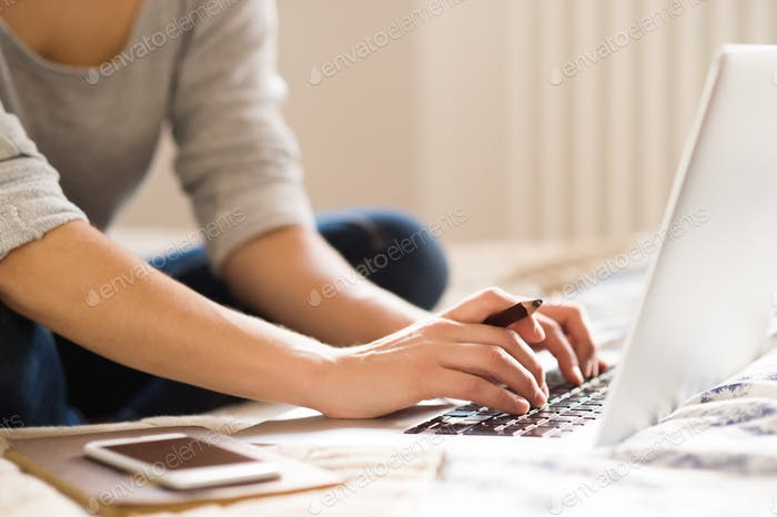 Unrecognizable young woman sitting on bed, working. Home office.