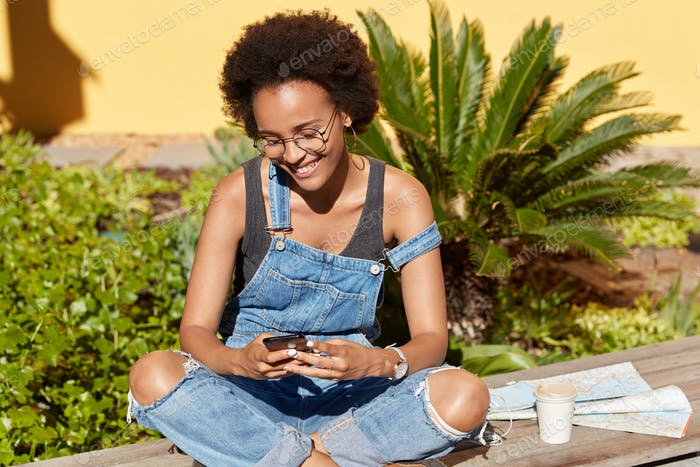 Positive female tourist uses contemporary cellular for sending messages in social networks, keeps le