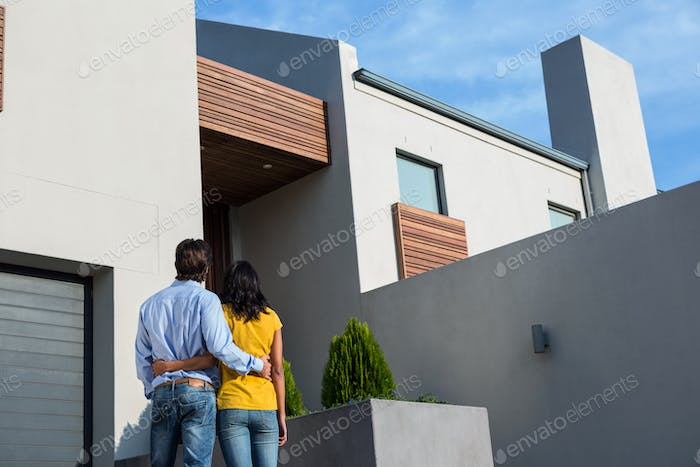 Happy Hispanic couple standing and looking at the new house