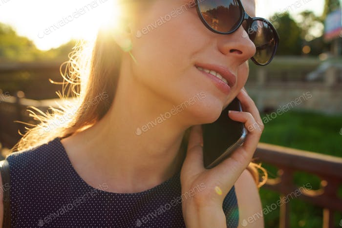 Frau in Sonnenbrille im Gespräch auf dem Smartphone beim Gehen nach unten