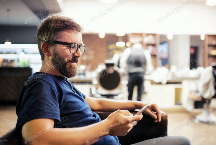 Hipster man client visiting haidresser and hairstylist in barber shop, waiting.
