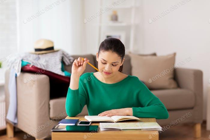 Frau mit Notizbuch und Reisekarte zu Hause