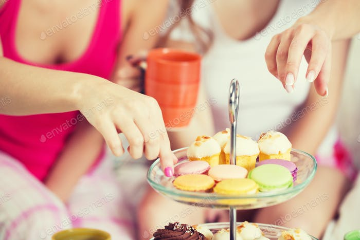 friends or teen girls eating sweets at home