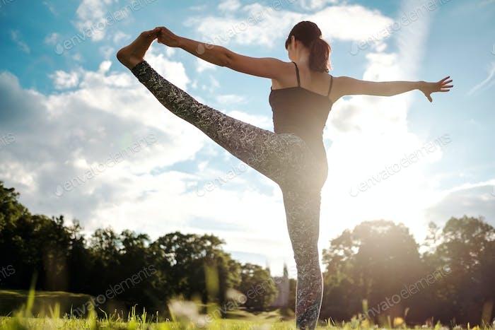 Caucasian woman in yoga standing balance Utthita Hasta Padangusthasana pose. Back view
