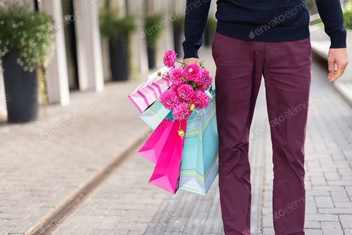 Romantic man with pink flowers and shopping bags on brick background. Woman's day. Valentine&#39