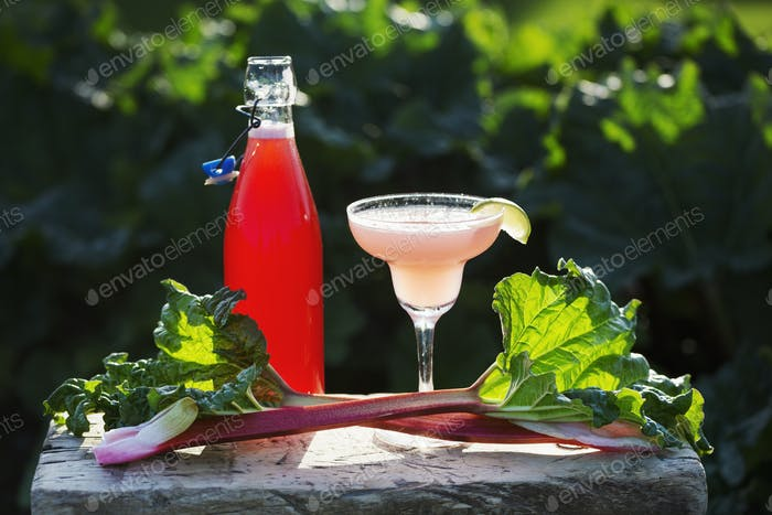 Close up of fresh rhubarb, a drinking glass and a glass bottle with a pink drink. A rhubarb