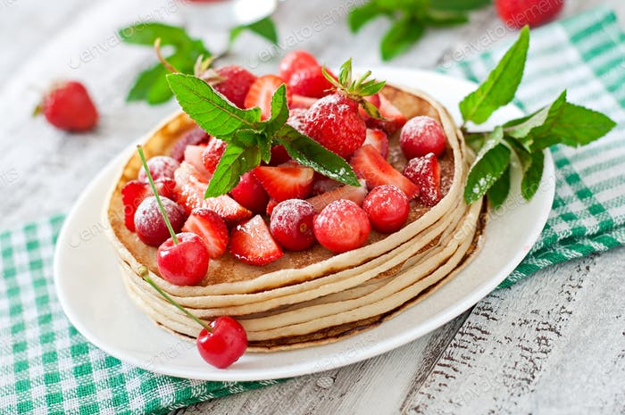 Pancakes with berries and strawberry smoothie in a rustic style