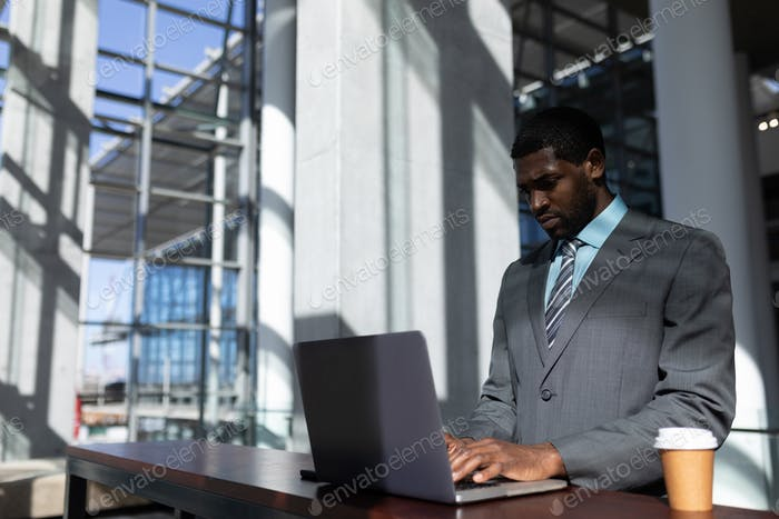 Businessman with coffee cup using laptop standing  in modern office