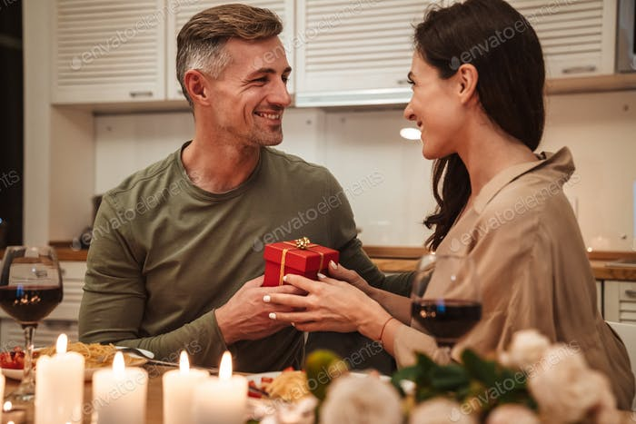 Image of man giving present box to his girlfriend during romantic dinner