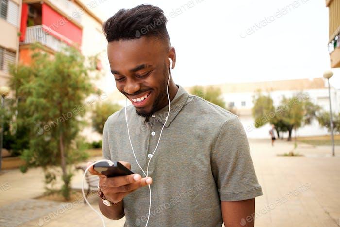 glücklicher junger Mann Musik hören mit Smartphone