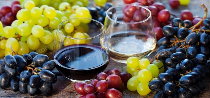 Glas Rot- und Weißwein mit frischem Traubensortiment auf Holztisch. Nahaufnahme.