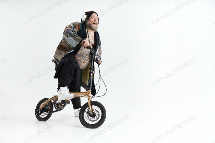 Big fat tattoed caucasian man in kimono is holding little bicycle and smilling