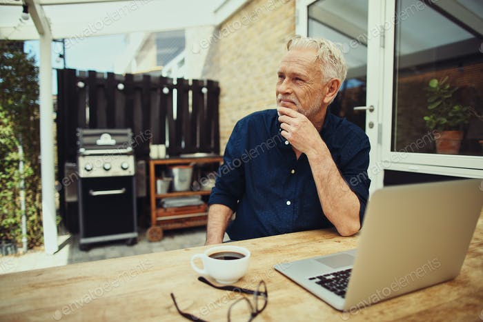 Content senior man sitting on his patio using a laptop