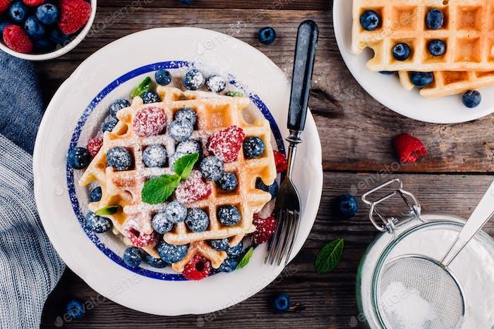 Fresh homemade belgian waffles with blueberries and raspberries for breakfast