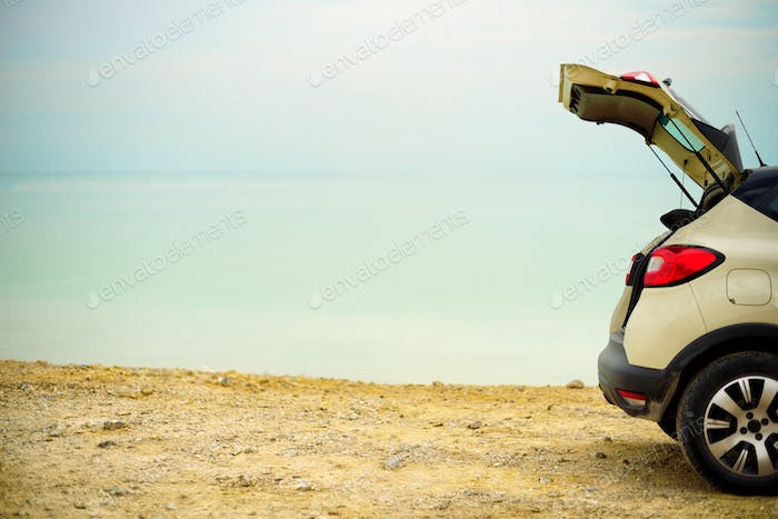 Summer vacation and holiday. Travel, adventure concept. White crossover car on beach road. Digital