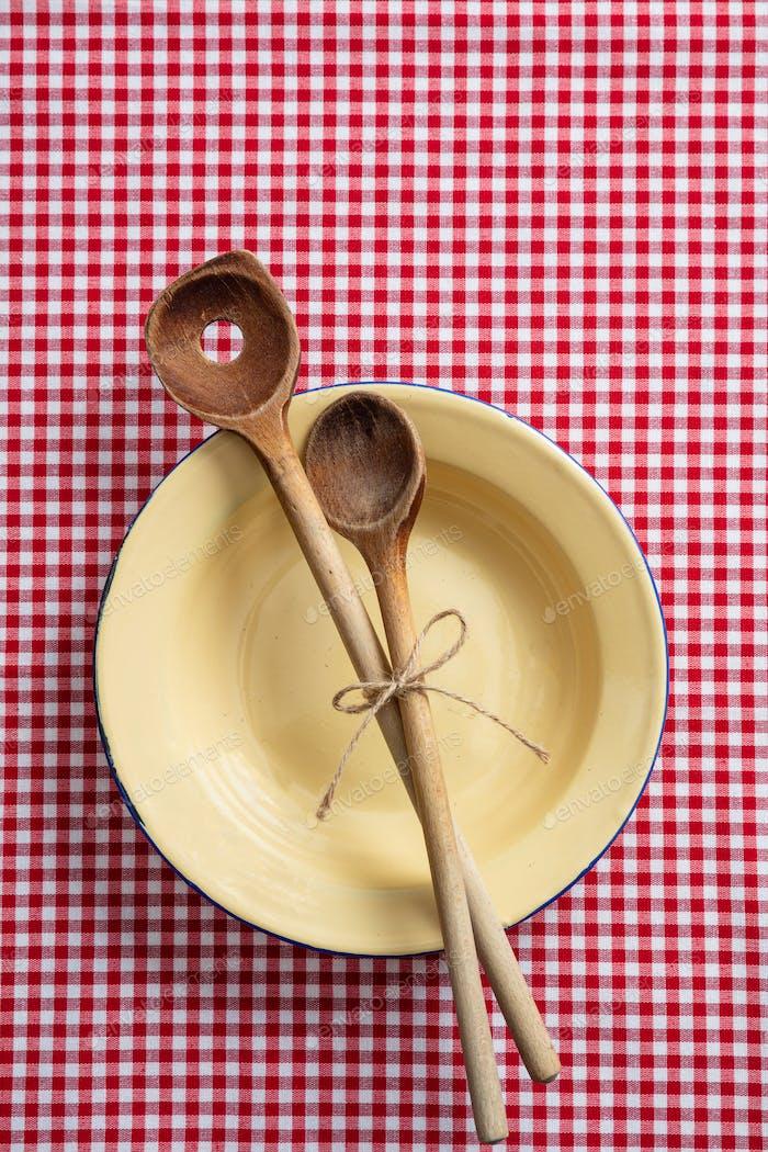 Leerer Teller, Küchenutensilien aus Holz und rote Tischdecke auf Holztisch, Draufsicht