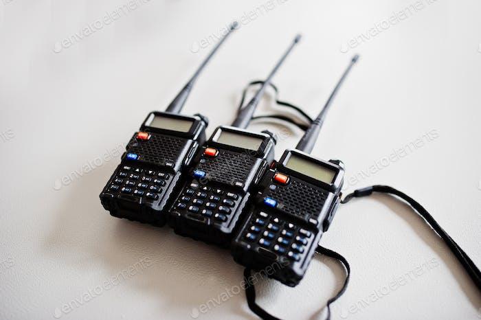 Tres transmisores de radio portátiles en fondo de acero.