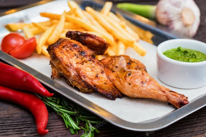 Close up meal with chicken thigh, french fries, chili pepper and garlic