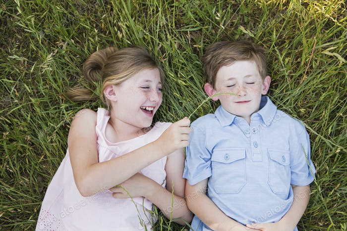 Two children, brother and sister lying side by side on the grass