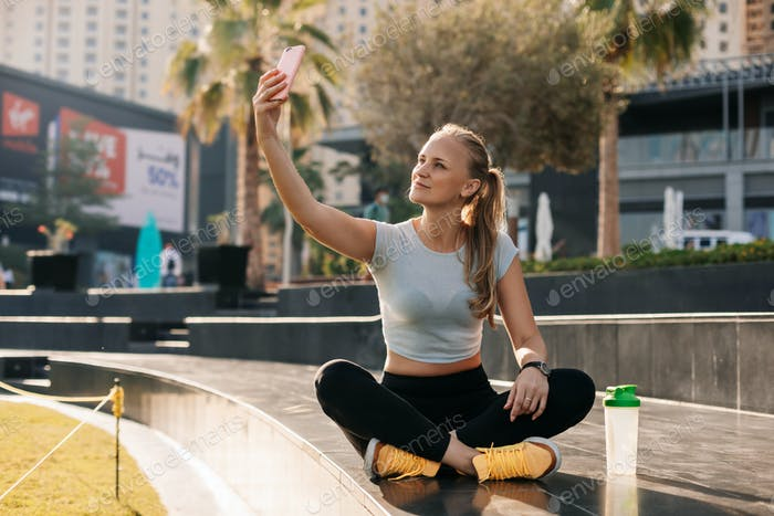 A young woman sits in a lotus position against the backdrop of a city landscape and takes a selfie