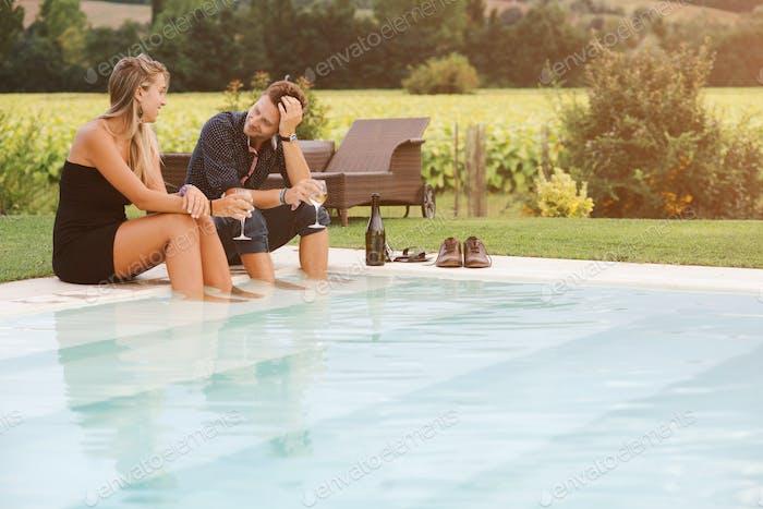 grupo de jóvenes amigos disfrutando de un partido piscina lado al atardecer
