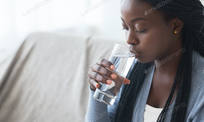 Thirsty black girl drinking clean water from glass at home