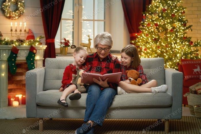 Großmutter liest Enkelinnen in der Nähe von Weihnachtsbaum.