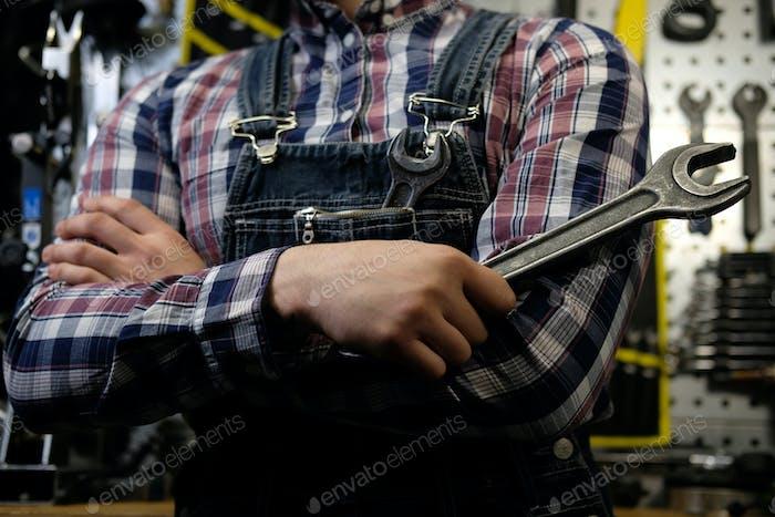 Красивый мужчина с бородой и стрижкой носить джинсы coverall работает в мастерской