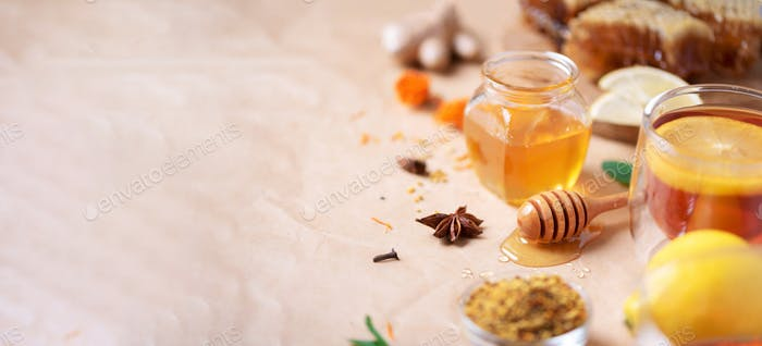 Ingredients for healthy hot drink. Lemon, ginger, mint, honey, apple and spices on craft paper