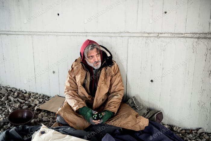A front view of homeless beggar man sitting outdoors, holding bottle of alcohol.