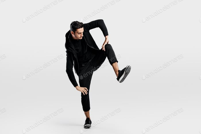 Young man dressed in a stylish black clothes lifts one leg up while dancing street dance