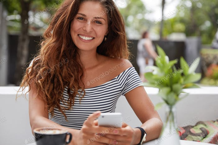 Attractive young woman recreats in favourite cafe, surfes internet on modern mobile phone, watches v