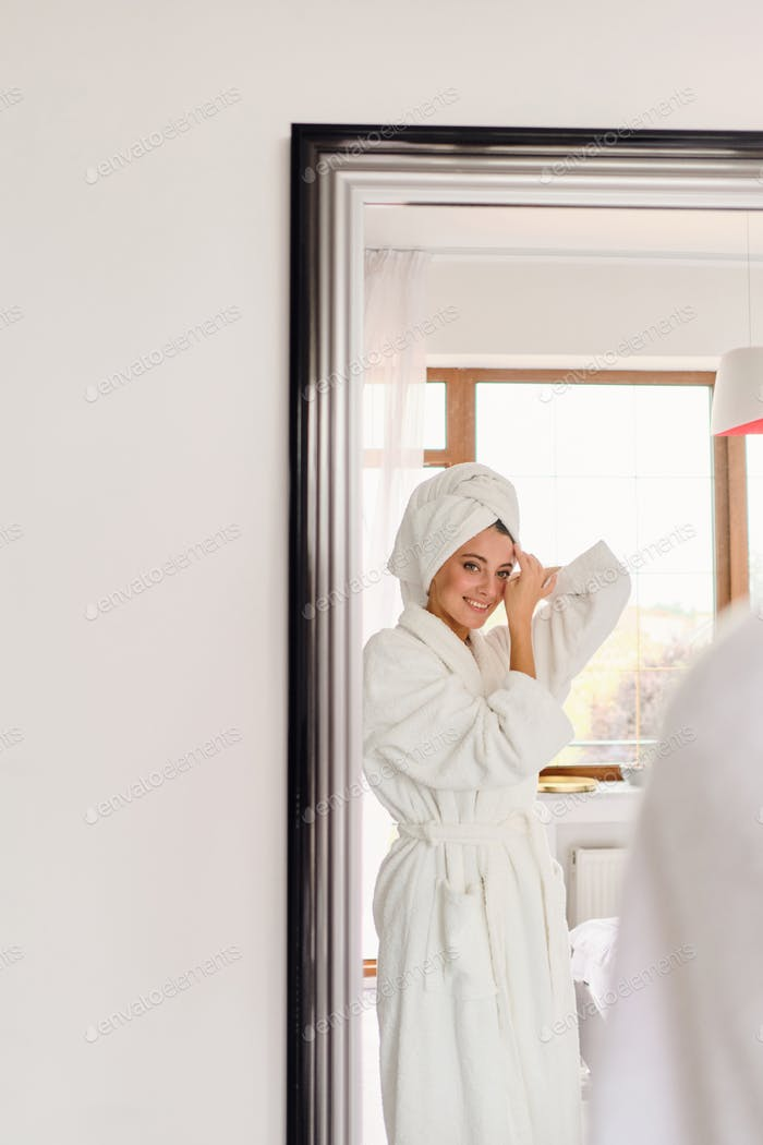 Smiling woman in white bathrobe and towel on head happily looking in mirror at modern hotel