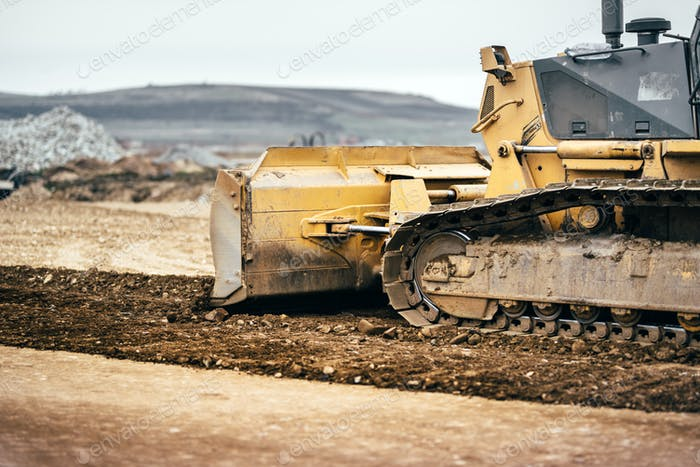 highway construction site development with bulldozer moving earth, soil and leveling ground