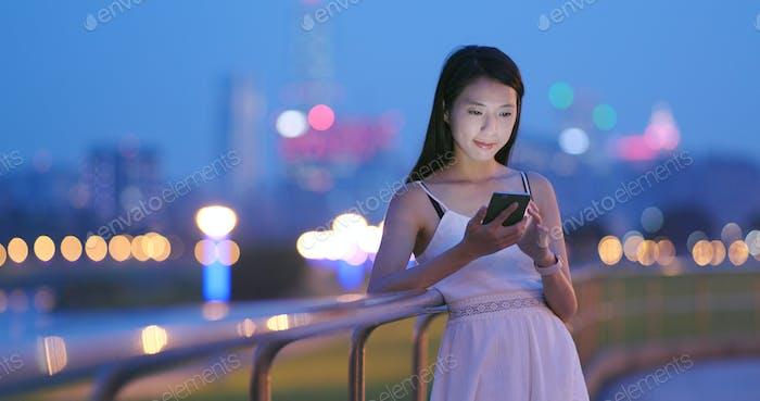 Asiatische Frau Nutzung des Mobiltelefons am Abend