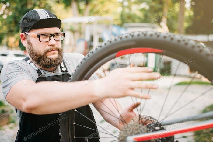 Bicycle repairman works with bike wheel