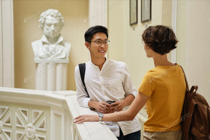 Two young attractive international students happily talking at break in university