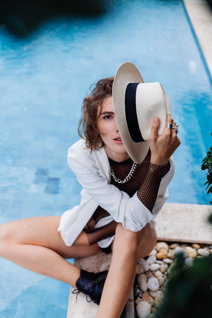 model in classic hat, black body suit and white blazer