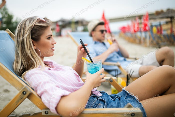 Happy couple relaxing and drinking on the beach on summer vacation