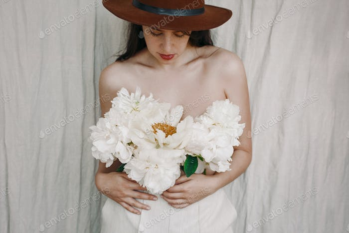 Sensual image of beautiful woman with peony bouquet instead of shirt