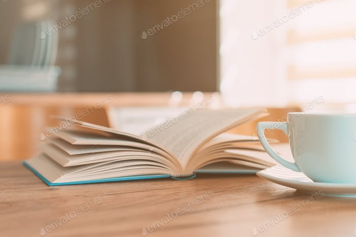 Open book and coffee cup on the table, reading at home in the morning