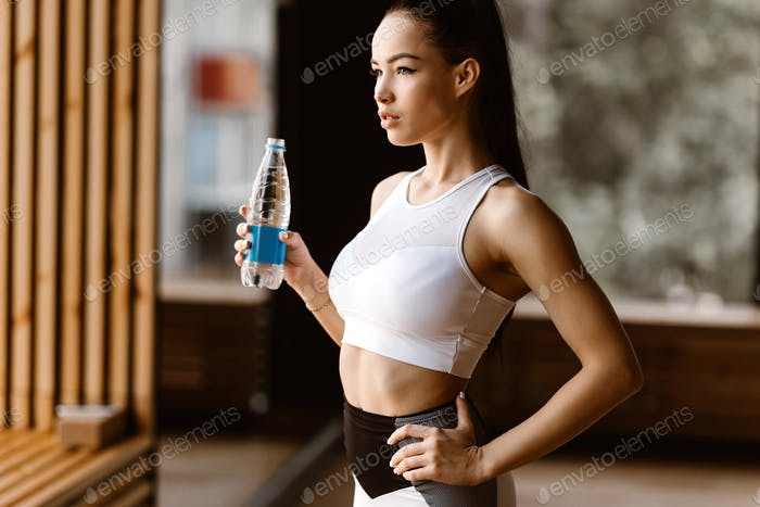 Beautiful slim dark-haired girl dressed in white sports top holds the bottle of water in the gym