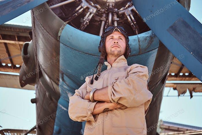 Proud aviator near jet's propeller.