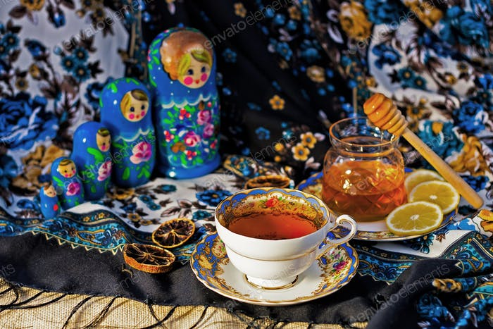 Tea set with lemon and honey on the colorful russian shawl and russsian dolls Matryoshka