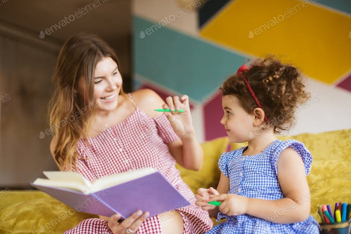 Beautiful mother with her little cute daughter joyfully reading