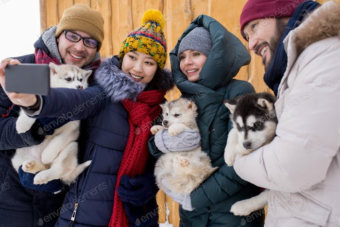 Friends Posing for Photo with Puppies