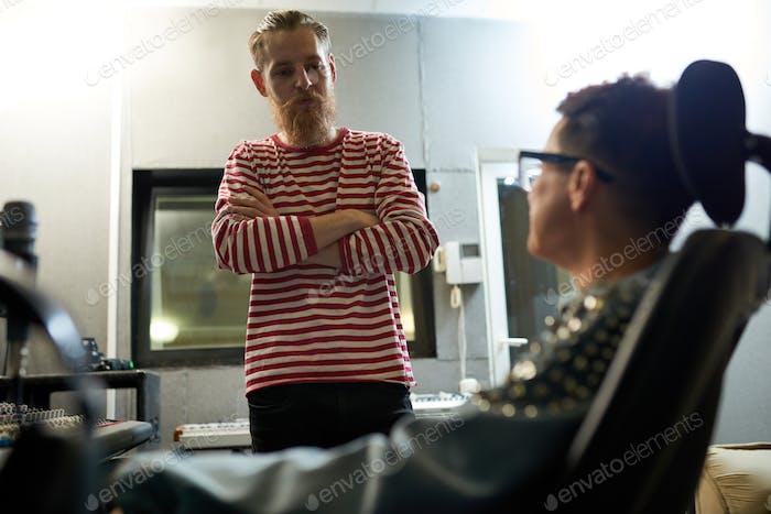 Trendy coworkers talking in recording studio