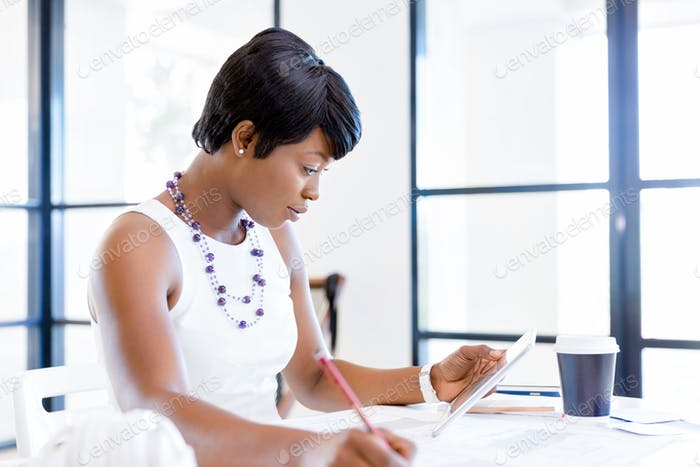 Young woman sitting at a desk in an office and working on blueprint