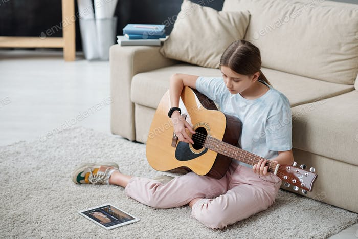 Pretty girl sitting on the floor by couch and learning to play guitar